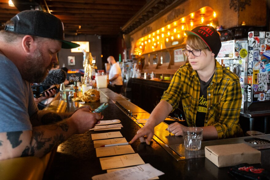 Nickel City bar manager Amanda Carto, right, goes over orders with co-owner Travis Tober on March 19. Tober is just hoping all the work going into reopening will pay off.