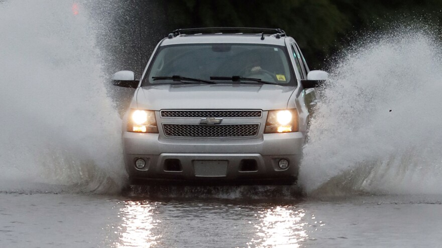 A vehicle drives through floodwaters in downtown Jackson, Miss., on Thursday, as strong winds and substantial rains added to the flash flooding throughout Mississippi.