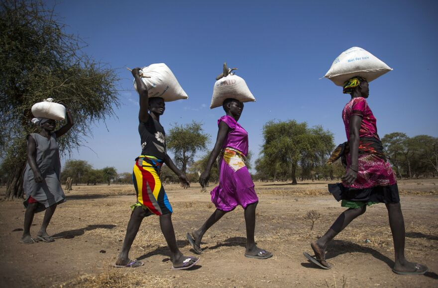 Women carry food in gunny bags after visiting an aid distribution center in South Sudan on March 10.