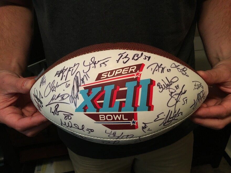 O'Callaghan holds a commemorative Super Bowl football autographed by the New England Patriots.  O'Callaghan played on the 2007-2008 Patriots team that almost went undefeated, losing only to the New York Giants in the Super Bowl.