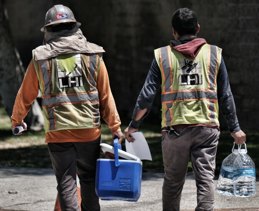 On a blistering hot day in southern California, construction workers carry large bottles of water during a break. Experts predict more intense and more frequent heat events across the country in coming decades, with huge implications for both indoor and outdoor workers.