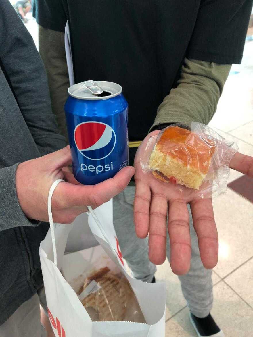 Two people hold a can of pepsi and a piece of cake.
