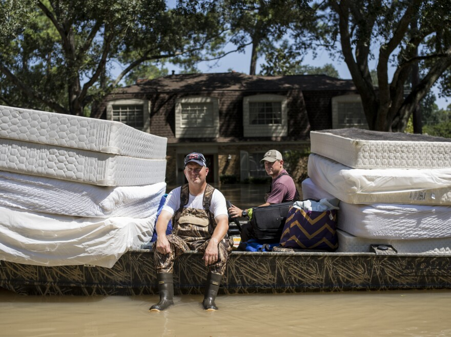 Scott McKnight (left) rides in a boat with his mattresses in the Nottingham Forrest subdivision of Houston on Thursday. Bret Hinkie, a Houston-area commercial airline pilot and a high school friend of McKnight, is volunteering to drive residents to their homes in his boat.