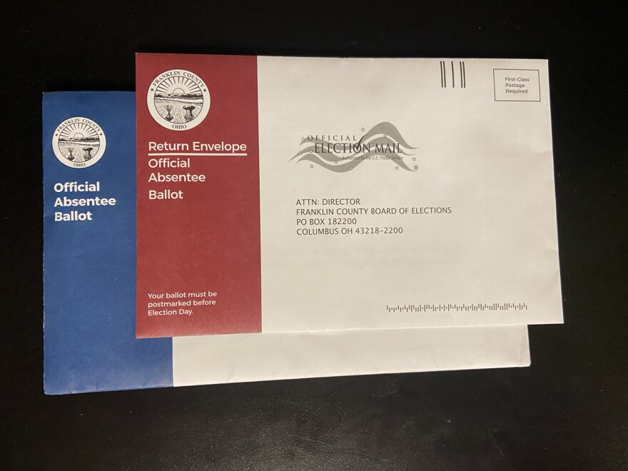 The blue absentee ballot packet features a red envelope to return the ballot in.