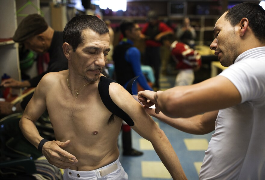 Azael De Leon helps Uriel Lopez wrap his shoulder as the jockeys prep for opening day.