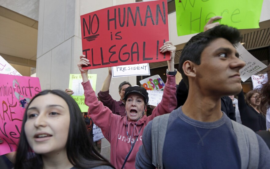 "A woman protests with a sign that reads ""NO HUMAN IS ILLEGAL."""