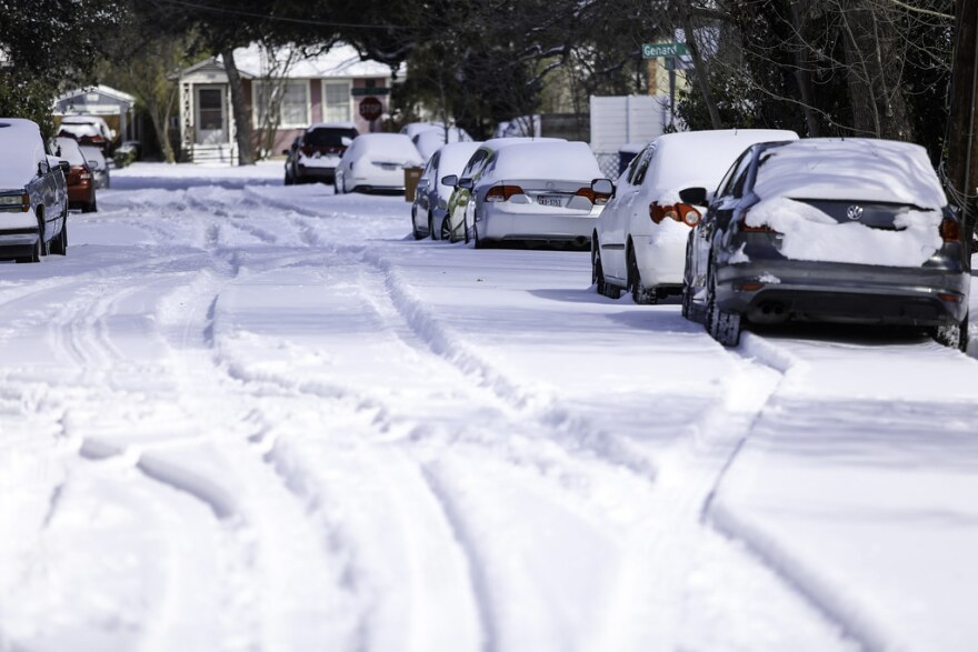 Tire tracks are carved into the snow on Zennia Street in the North Loop neighborhood of Austin.