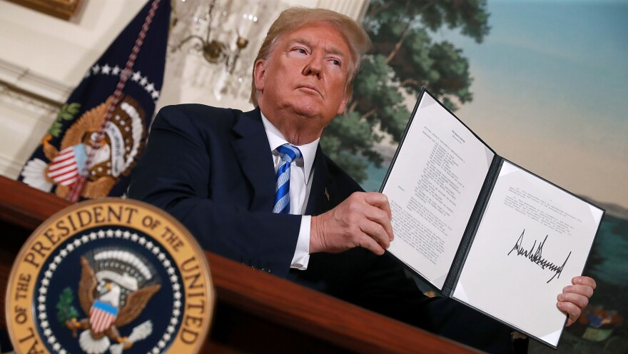 President Trump displays a memorandum Tuesday marking his decision to withdraw the U.S. from the 2015 nuclear deal. Moments later, as he left the Diplomatic Room at the White House, he told reporters that Secretary of State Mike Pompeo was on his way to North Korea.
