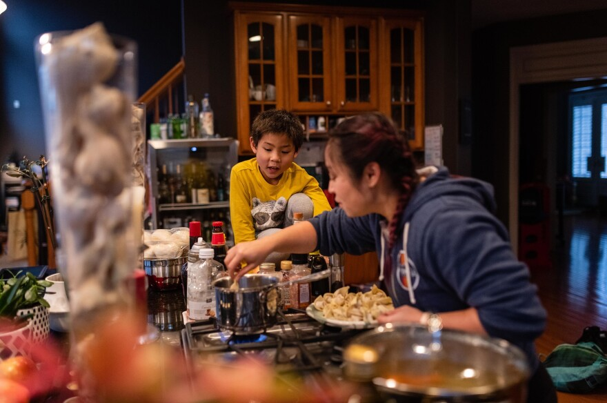 Thu drops in dumplings for Lunar New Year celebrations as Hayle checks on the pot of boiling water on Jan. 26, 2020.