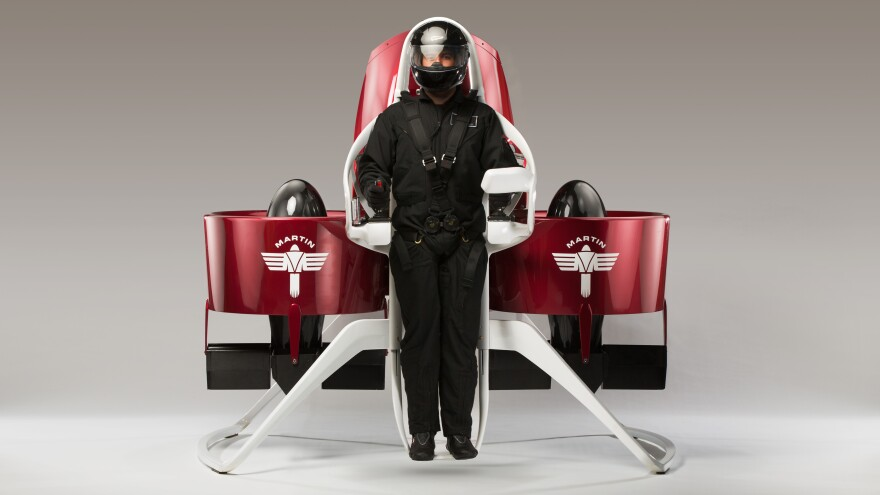 Standing on the center console of the Martin Jetpack, a pilot straps in and uses the joysticks to control flight.