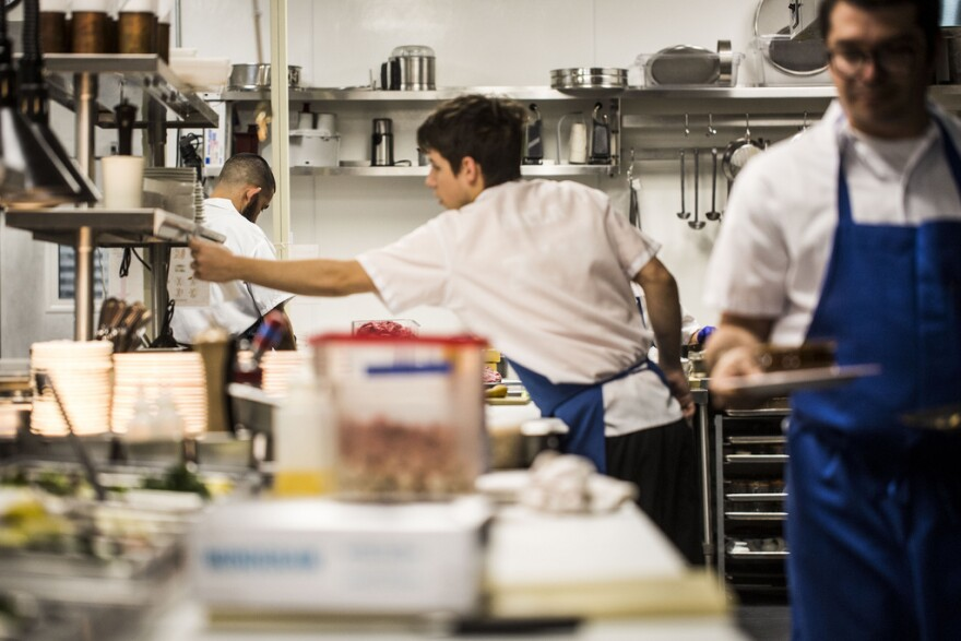 The kitchen staff prepares meals at Le Politique in downtown Austin.
