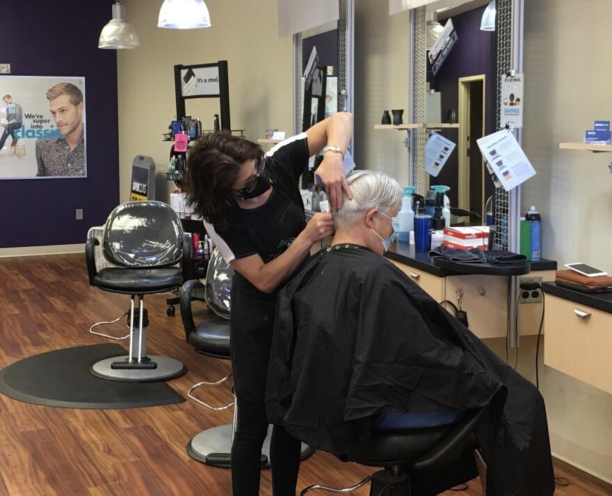 Marissa Segallos cuts a customer's hair at SuperCuts in Oldsmar.
