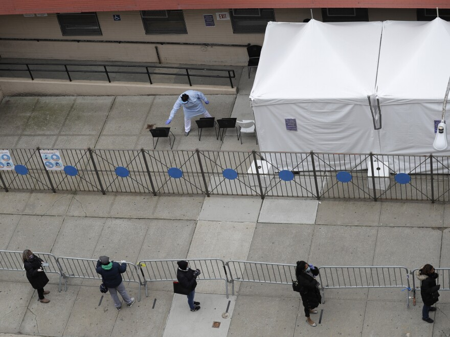 People stand in line at a coronavirus testing site in Harlem. In an effort to test more people for the virus, New York and other cities have begun offering door-to-door screening and at-home testing.