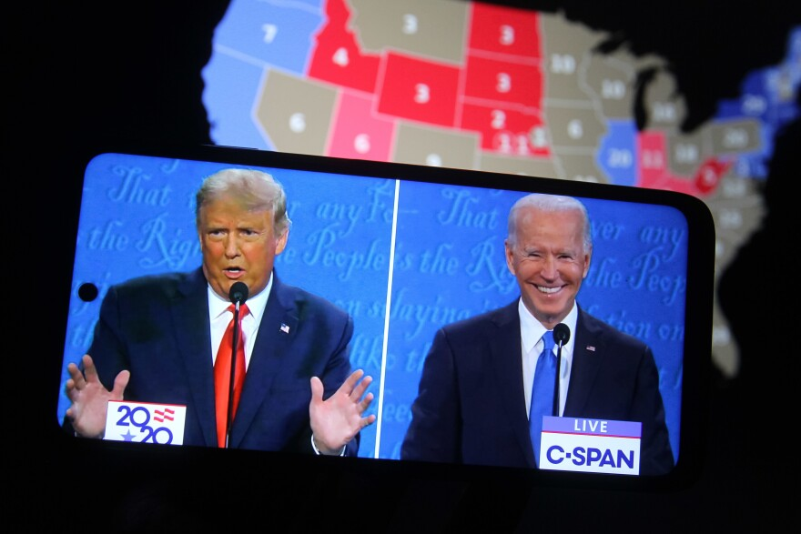 Some major final steps for the 2020 census are set to take place during the transition from President Trump to President-elect Joe Biden, who appear on a smartphone displaying the final presidential debate in October.