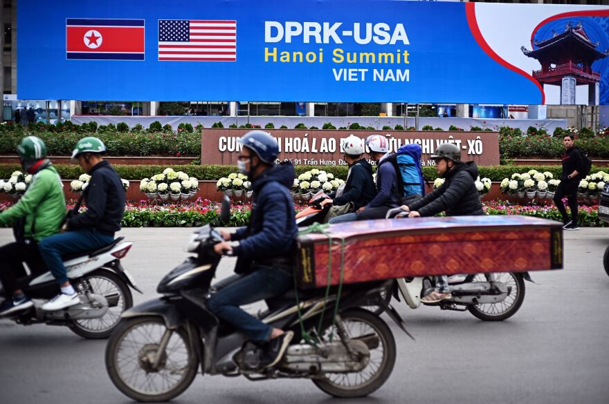People ride past a billboard in Hanoi for the second summit between President Trump and North Korean leader Kim Jong Un.