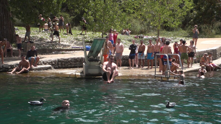 A man jumps from the diving board at Barton Springs Pool in August.