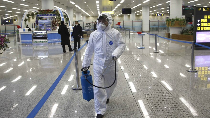 North Korean State Commission of Quality Management staff in protective gear carries a disinfectant pray can as personnel check the health of travelers and inspect goods delivered via the borders at the Pyongyang Airport in North Korea, on Feb. 1.