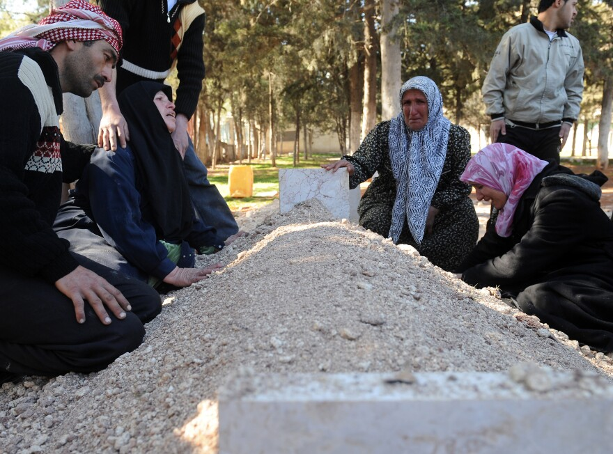In February, these Syrians mourned over the fresh grave of a relative following a funeral for victims killed in violence in Idlib.