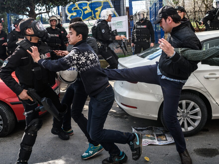 A plainclothes police officer kicks a demonstrator as Turkish anti-riot police disperse supporters in front of the headquarters of the Turkish daily <em>Zaman</em> newspaper in Istanbul on March 5. Turkish authorities seized the headquarters in a midnight raid.