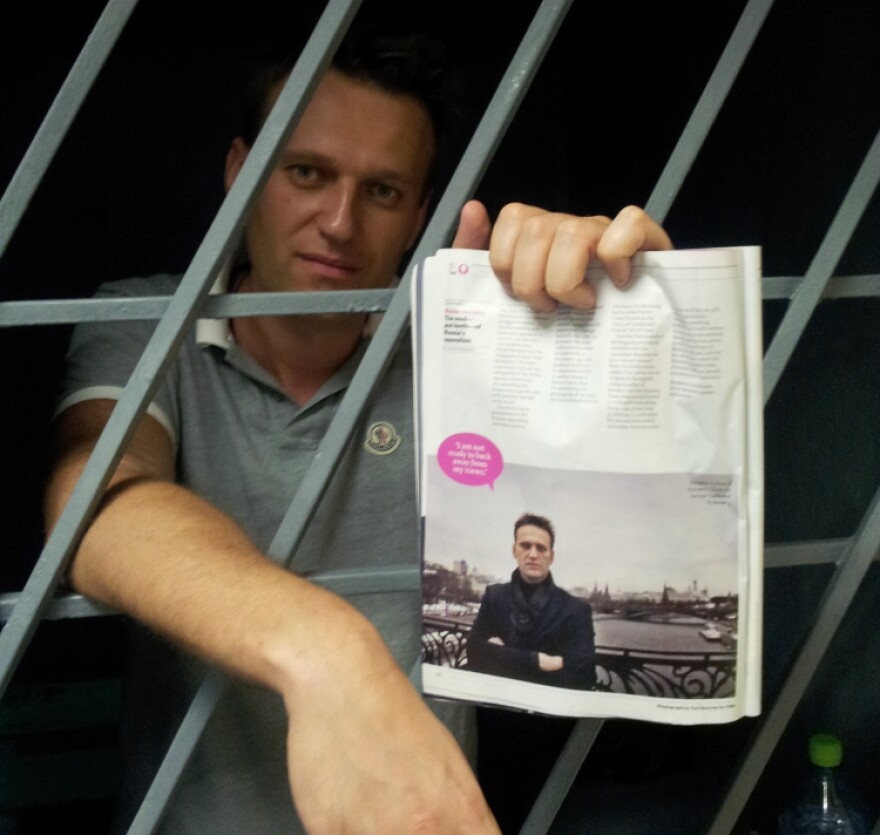 Alexei Navalny, a prominent anti-corruption whistleblower and blogger, holds an issue of <em>Time</em> <em>Magazine</em>, with his photograph, as he stands behind bars in a prison after he was detained in Moscow on Sunday.