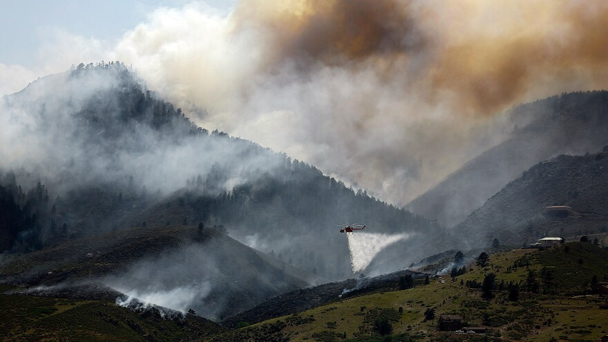 Near Laporte, Colo., earlier this week, smoke billowed from the mountains. In the foreground: A helicopter was dumping water on a hotspot.