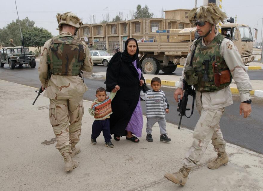 An Iraqi woman holds the hand of two children as she walks past two U.S. soldiers after they briefly stopped a vehicle at an intersection in downtown Tikrit, north of Baghdad, on Nov. 10, 2003.