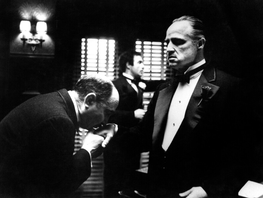 Amerigo Bonasera (Salvatore Corsitto) kisses the hand of Don Vito Corleone (Marlon Brando) in a scene from Francis Ford Coppola's <em>The Godfather</em>.