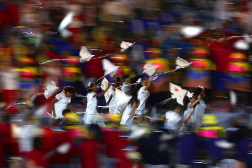A group of children run onto the stage carrying small dove kites with Kipchoge Keino, 72 — a former Olympian who won two gold medals and is now the chairman of the Kenyan Olympic Committee. Keino is the first-ever winner of the Olympic Laurel award.