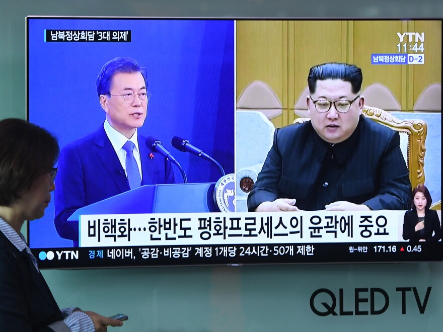 A woman walks past a news screen showing file footage of South Korean President Moon Jae-in and North Korean leader Kim Jong Un at a railway station in Seoul this week. Kim will walk across the Demilitarized Zone on Friday for a historic summit with Moon.