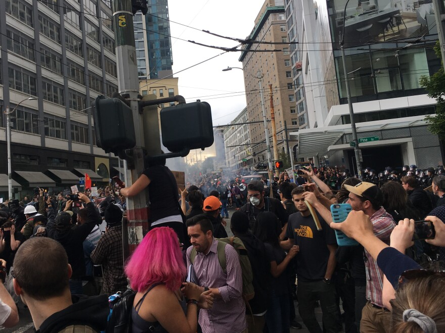 Demonstrators in Seattle scatter after hearing a loud bang, apparently from a police riot control device. Protesters who had gathered to counter a pro-Trump rally Sunday had a tense standoff with local police, who sought to keep the two groups separate.