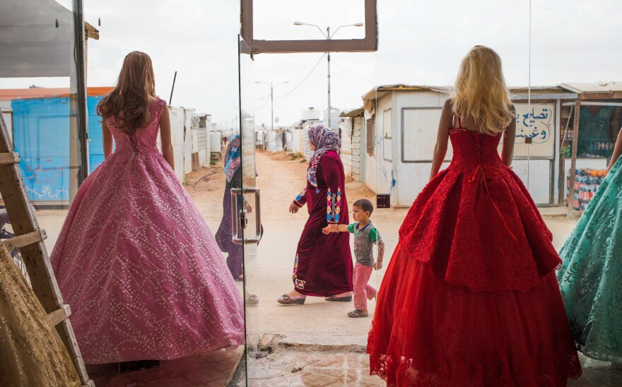 Wedding dresses come in bold hues at Salon Al Fardous — Paradise Salon. The rent-a-gown shop looks out on the temporary housing and makeshift stores in the Zaatari refugee camp in Jordan.