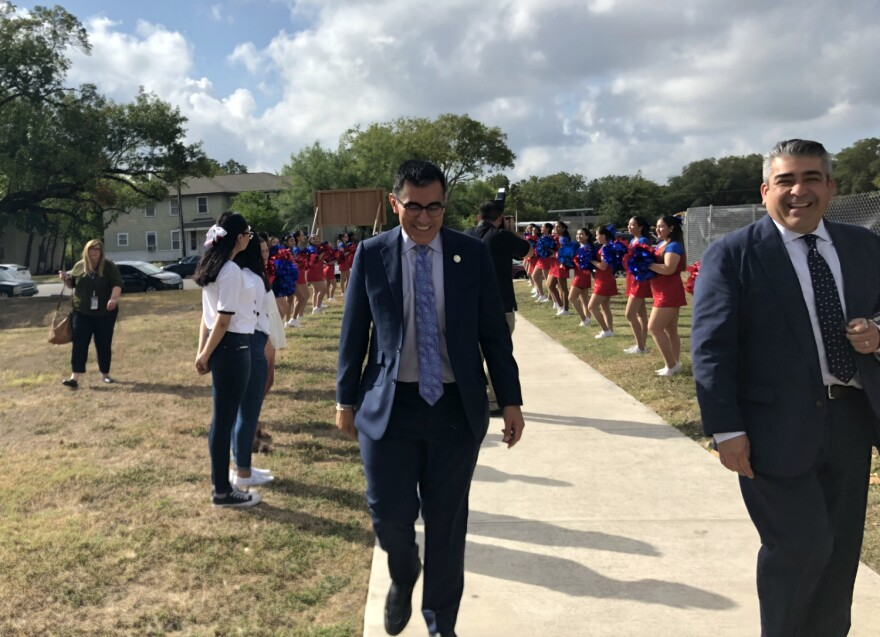Alamo Colleges Chancellor Mike Flores, center, is greeted by Jefferson High School cheerleaders as he arrives at the launch ceremony for AlamoPromise Oct. 2, 2019.