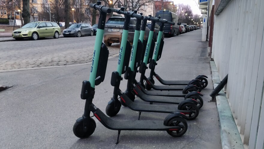 Electric scooters stand in a row.