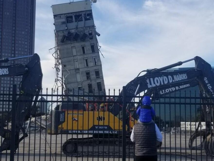 James looks at the leaning tower from his dad's shoulders before demolition begins.