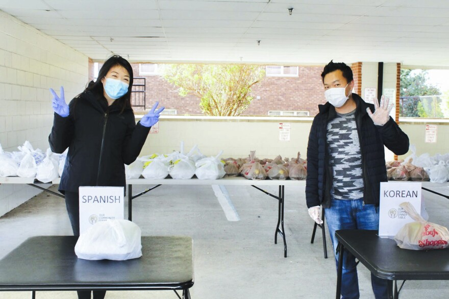 Volunteers Soojung Kwak and Pastor Bob Koo prepare to distribute meals for Our Community Dinner Table.