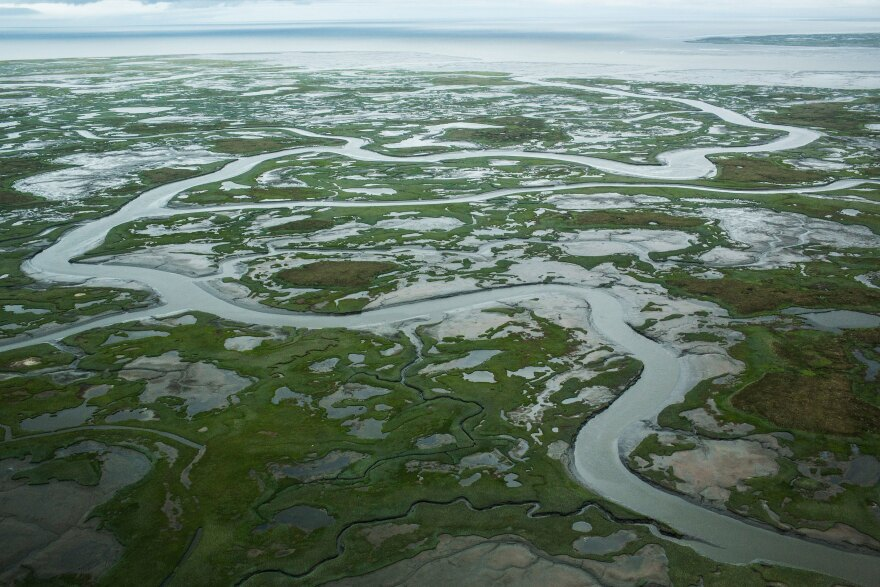 A marshy tundra landscape surrounds Newtok in the warmer months. The increased melting of sea ice is causing the Ninglick River to widen, eroding the riverbank. Larger storms that come in from the Bering Sea further erode the land.