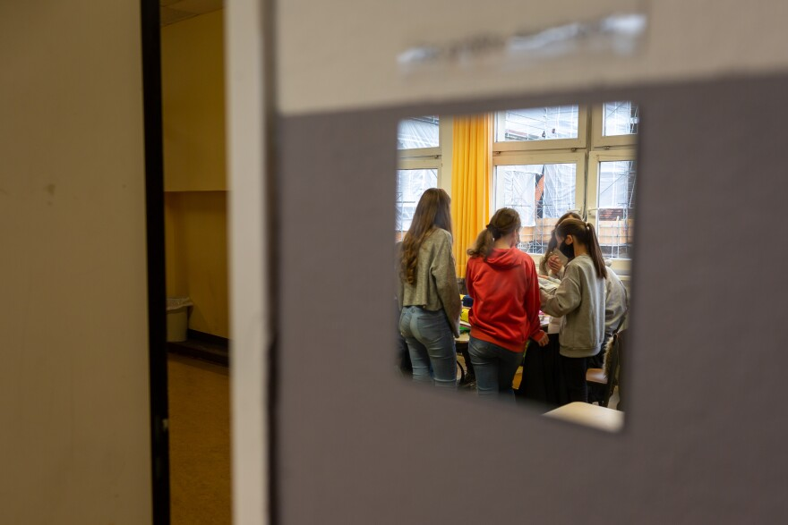 Students working on a book project at the Fritz-Karsen-Shule in Berlin are reflected in a mirror on the classroom wall on Oct. 26, 2020.