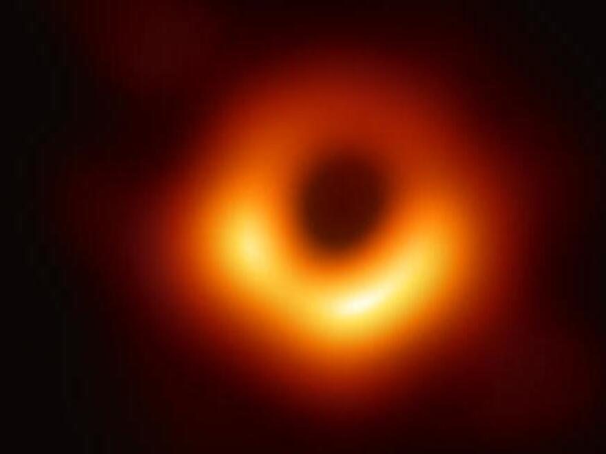 The first-ever image of a black hole  at the center of galaxy M87, outlined by emission from hot gas swirling around it.
