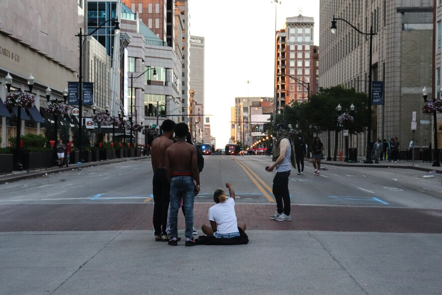 A woman sits in the street with her fist raised while police gather on High Street.