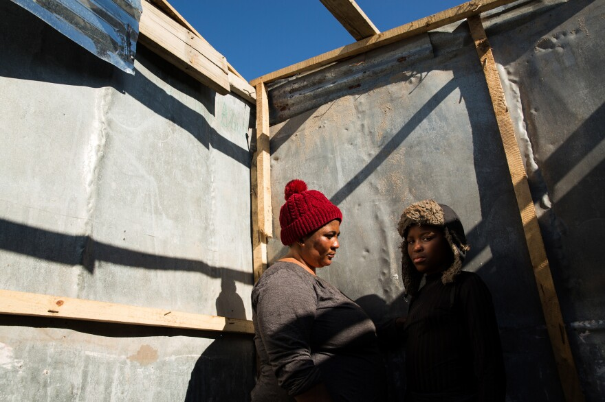 "Noluthanda Gwanya and her daughter Inathi Sigijimi, 12. A storm the night before flooded their shack and blew off the roof, and they had to shelter with friends. ""I don't want promises anymore. Just take us to the right place. We're hungry in the head and in the stomach,"" said Gwanya."