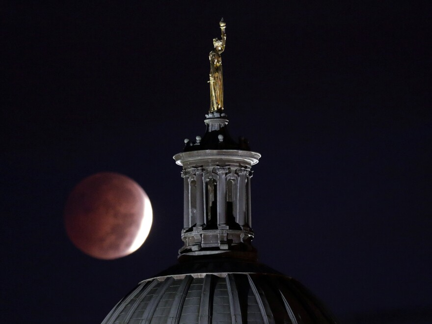 """The eclipse as seen near the """"Enlightenment Giving Power"""" statue by John Gelert, which sits at the top of the dome of the Bergen County Courthouse in Hackensack, N.J."""