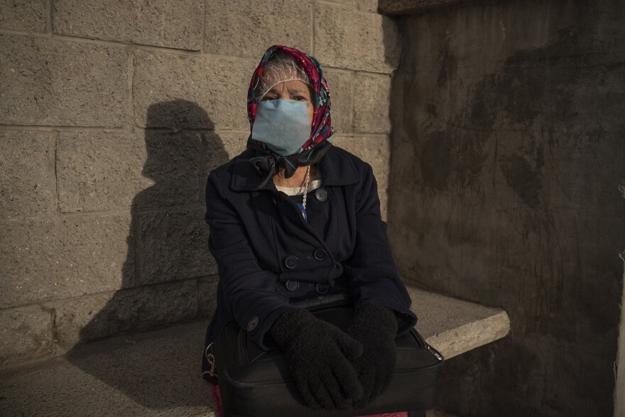 Maria, 68, from Cuba wears makeshift personal protective equipment after presenting at the Paso del Norte International Bridge on March 26, 2020.