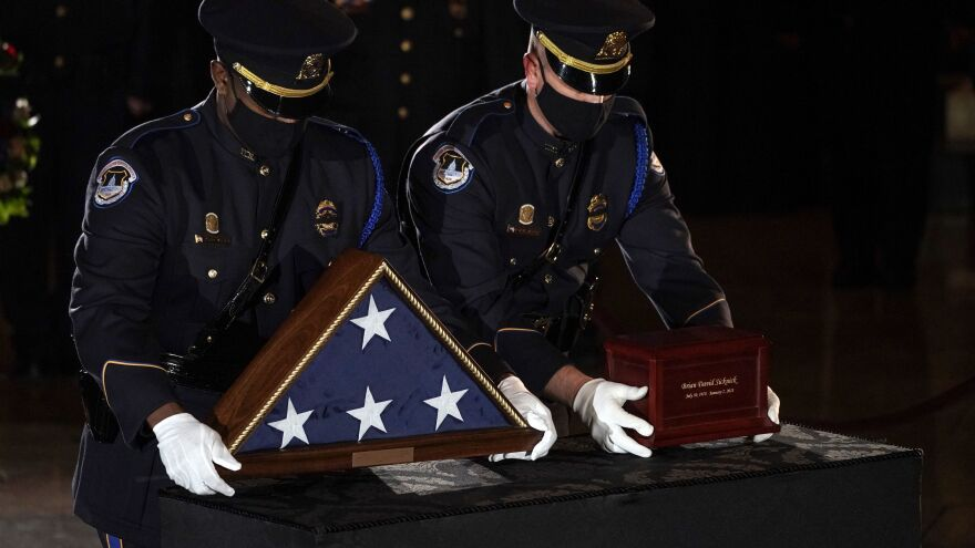 Sicknick's remains are placed next to a U.S. flag on a pedestal in the Capitol Rotunda