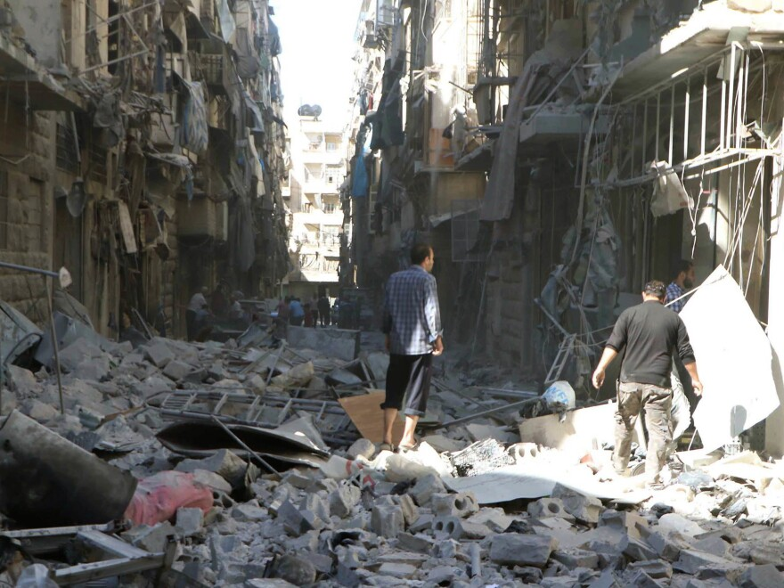 In a photo provided by the Syrian Civil Defense group known as the White Helmets, men inspect damaged buildings in Aleppo, Syria, on Saturday.