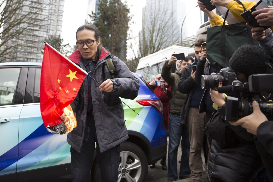 Kuang Yang burns a Chinese flag to protest human rights abuses, outside British Columbia Supreme Court in Vancouver on March 6, as Huawei Chief Financial Officer Meng Wanzhou appears in court.
