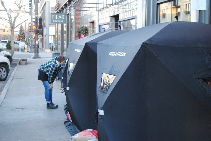 A waitress wearing a mask stands outside black tents set up on the sidewalk in front of businesses and restaurants.