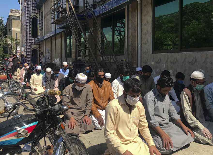 Dozens of worshippers pray outside the Haidari Mosque in the Pakistani capital of Islamabad.