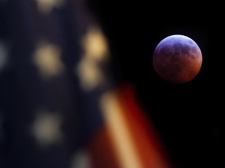 A U.S. flag flies in the foreground of this image of the moon during the lunar eclipse as seen from Washington, D.C., on Sunday night.