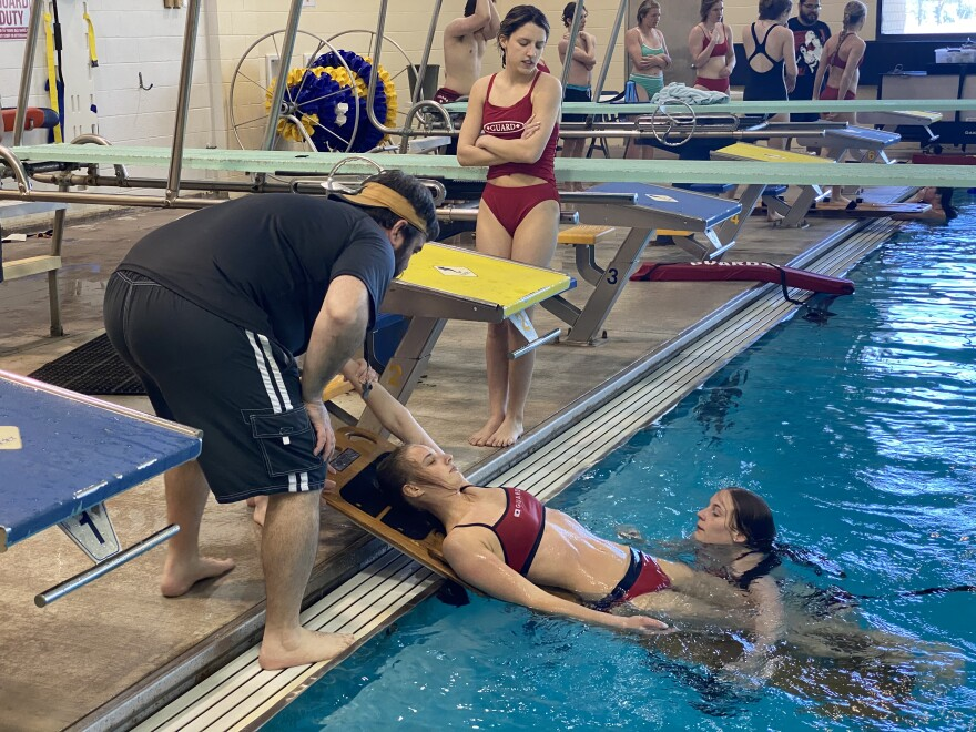 Brian Hill, left, shows lifeguard trainees how to place a victim onto a backboard. Hill manages the aquatics program for the city of Wichita.