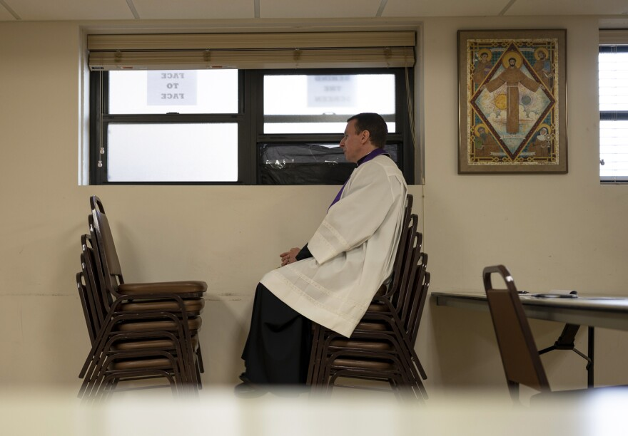 Father Anthony Yates sits on top of a stack of chairs, waiting for congregants to arrive at the drive-thru confession on May 11, 2020.